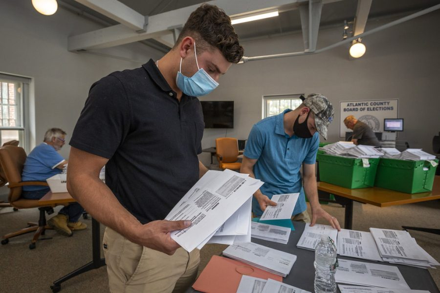Poll workers handle voters' mail-in ballots in protective masks. Source: Creative Commons
